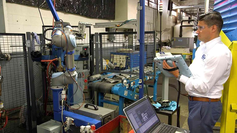 Man programming collaborative robot for welding application