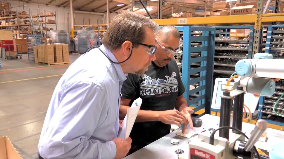 "Birk Sorensen(left), VP of Engineering at EMTEK, oversees the gluing process. ""The return on investment was just shy of 12 months, so it had worked out to be very advantageous for us,"" he says."